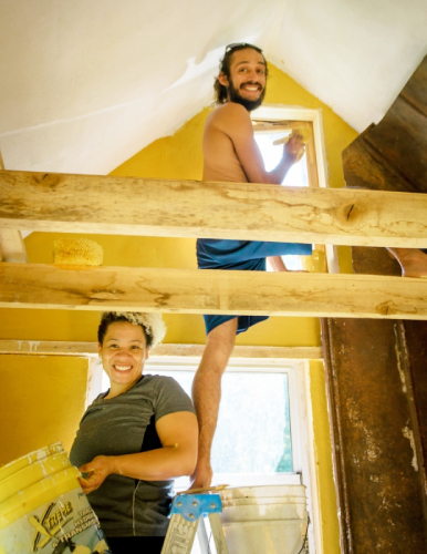 building students using earthen paint in tiny house