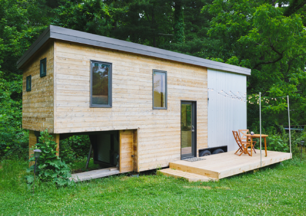 stylish tiny house with front deck and lush green lawn