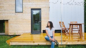 woman sitting on front deck of a tiny house
