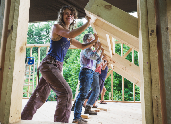 online tiny house class instructor and students raising a wall