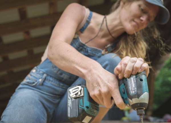 woman using impact driver to build a tiny house