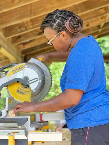 woman using chop saw to cut lumber for tiny house