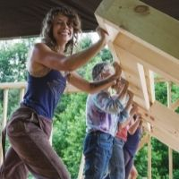 women raising a wall in a tiny house