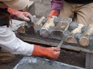 details of hands working on cordwood construction